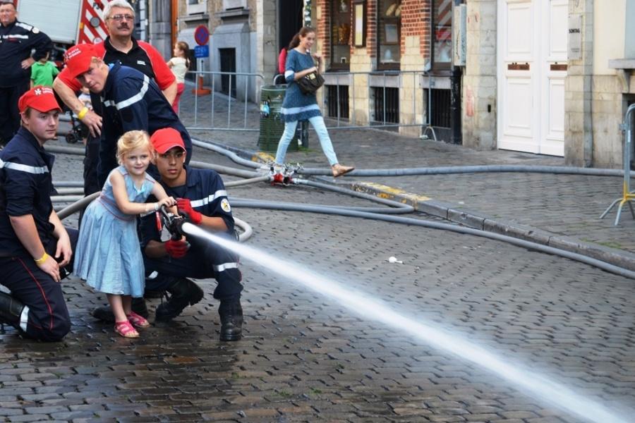 Jugendfeuerwehr lehrt Kinder, einen Feuerwehrschlauch festzuhalten